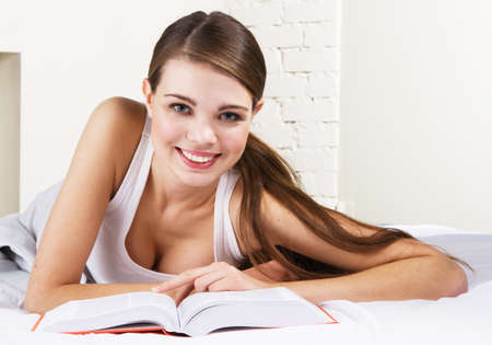 wakeup: Young beautiful woman reading a book in bed Stock Photo