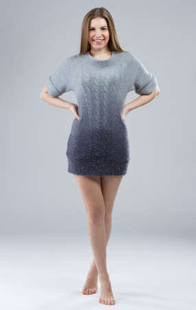 Beautiful elegant model in woolen sweater on gray background  photo