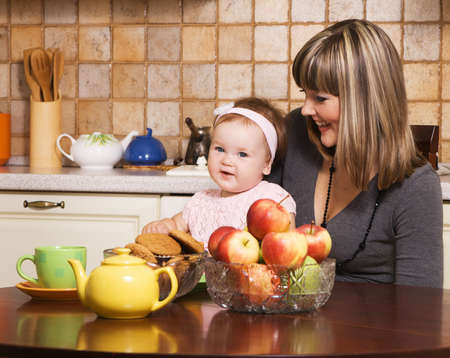 Happy young mother with her little daughter at kitchen  photo
