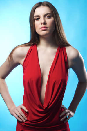 Gorgeous model in elegant red gown against blue background  photo