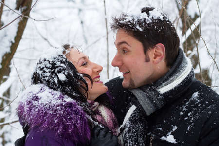 Portrait of young happy couple in winter park photo