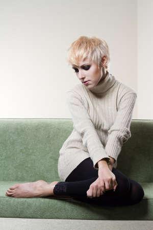 короткие волосы: Portrait of young beautiful woman sitting on sofa alone
