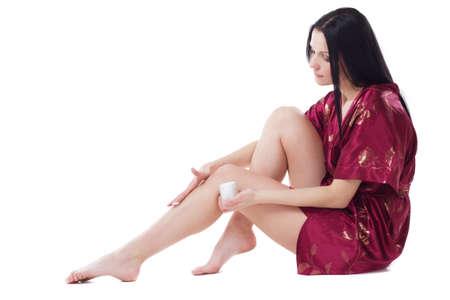 pieds sexy: Belle femme appliquant des corps cr�me sur ses jambes attrayants, isol�s sur fond blanc Banque d'images