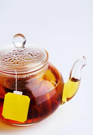 Teapot of hot black tea on white background