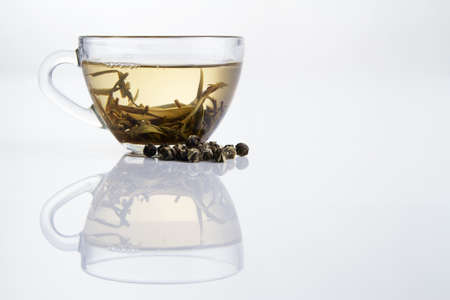 Glass cup of fresh white tea with dry tea granules photo