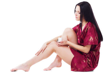 foot cream: Beautiful woman applying body cream on her attractive legs, isolated on white