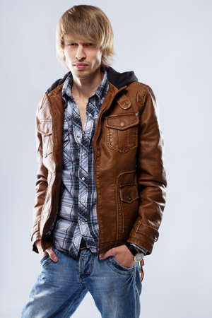 blond brown: Handsome young man in leather jacket, studio portrait