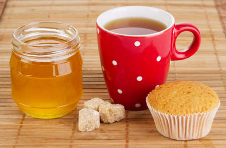 Cup of sweet tea with cakes and honey photo