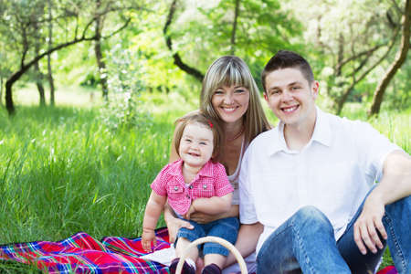 Young beautiful family of three on a picnic photo