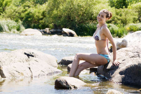 Young sexy woman, posing on a rock photo