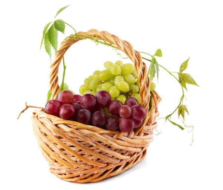 Wicker basket with grapes isolated on white background photo