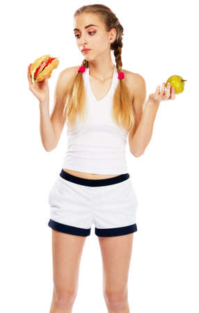 endure: Young woman holding a hamburger and an apple, white background