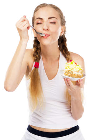 Young lady tasting a cake, studio portrait photo