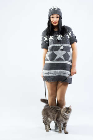 Young lady with a cat, studio photo on neutral backgrund photo