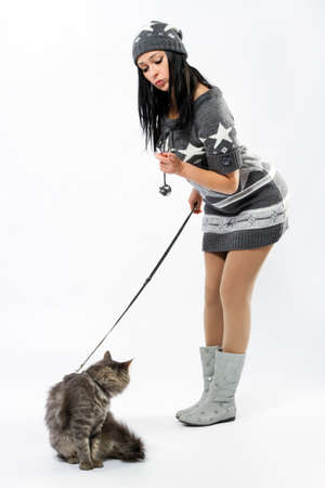 scold: Young lady with a cat, studio photo on neutral backgrund
