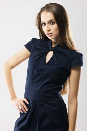 Beautiful fashion model in strict blue dress, gray background photo