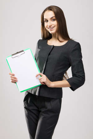Businesswoman in strict clothing, neutral background photo