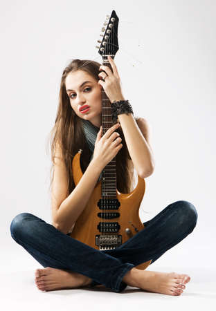 Beautiful girl with electric guitar, neutral background photo