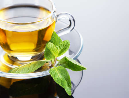 brown cup tea: Tea cup with fresh mint leaves, closeup photo Stock Photo