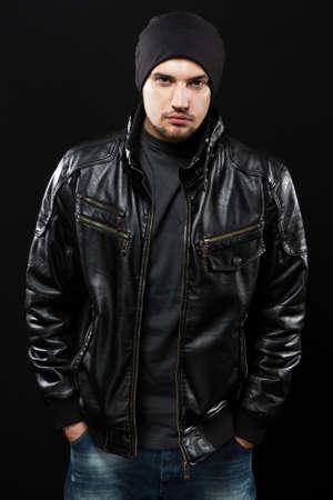 chaqueta de cuero: Apuesto joven en chaqueta de cuero negro, retrato de estudio