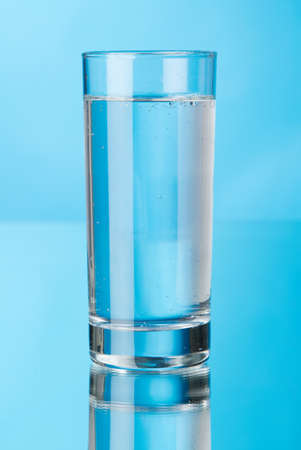 Glass of water on blue background, studio picture photo