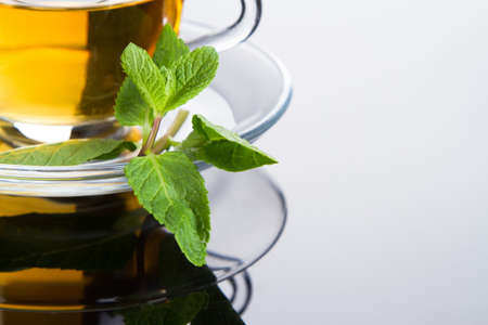 Tea cup with fresh mint leaves, closeup picture photo