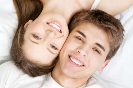 toothy: Beautiful young couple in bed, face portrait
