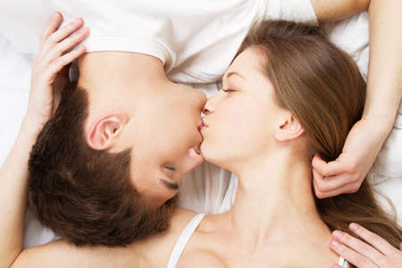 baiser amoureux: Belle jeune couple au lit, portrait visage Banque d'images
