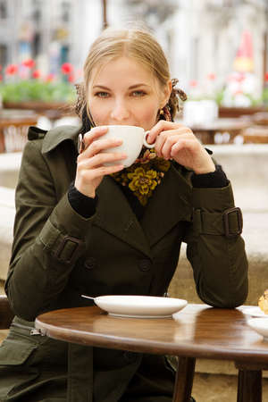 Beautiful woman drinking coffee in outdoor cafe photo