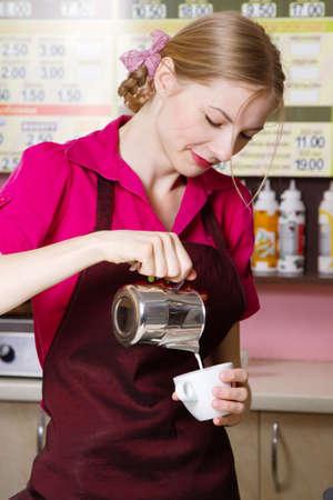 Friendly waitress making coffee at coffee machine photo