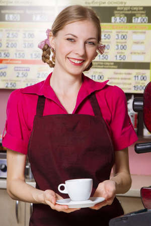 Friendly waitress making coffee at coffee machine photo