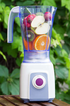 Electric blender with fruits in it, green leaves background photo