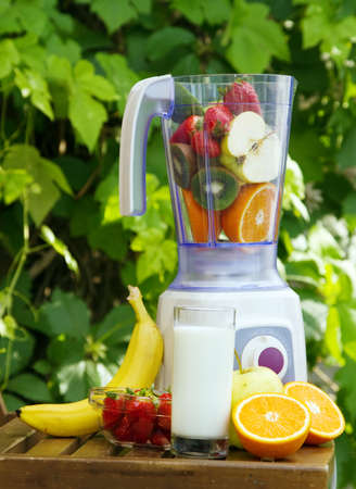 blending: Electric blender with fruits in it, green leaves background Stock Photo