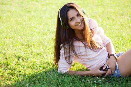 Beautiful woman in headphones sitting in grass photo