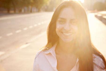 Beautiful lady in sunset light walking along the street Stock Photo - 14344957