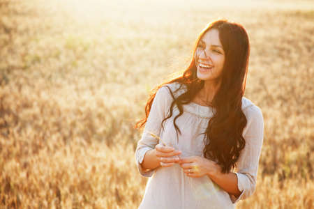 wheat fields: Beautiful brunette lady in wheat field at sunset