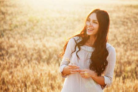 mujeres felices: Bella dama morena en el campo de trigo al atardecer