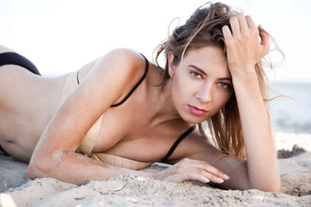 Beautiful model lying in sand on a beach photo