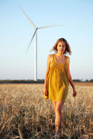 Lady walking in the field with wind power generator on background Stock Photo - 14344949