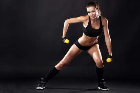 Beautiful slim woman with dumbbells, black background photo