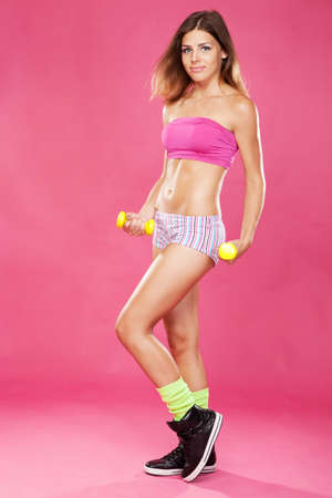 Beautiful slim woman with dumbbells, pink background Stock Photo - 14432784