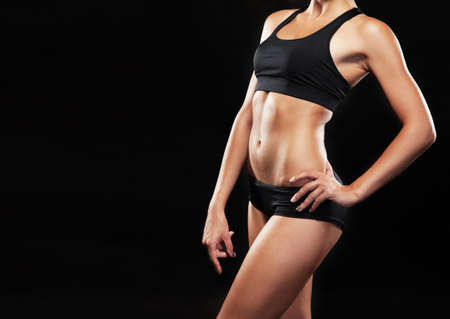 Young fit woman in sports outfit, black background photo