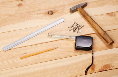 Carpenters tools on pine desks, closeup photo