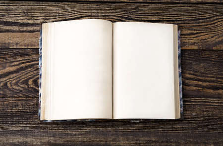 Aged blank book on wooden table, blank pages photo