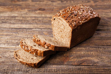 Brown bread on an old wooden table photo