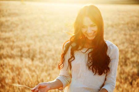 Mooie brunette dame in tarwe veld bij zonsondergang