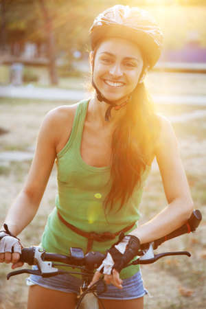 Beautiful young slim woman riding a bicycle photo
