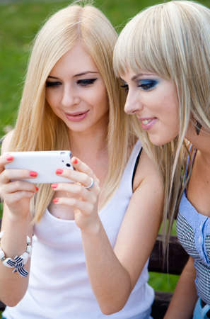 Two girl friends using a modern smartphone photo