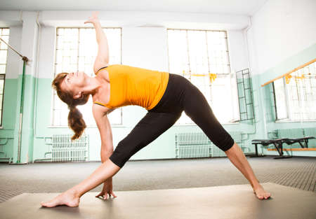 Mature woman exercising yoga in a gym photo
