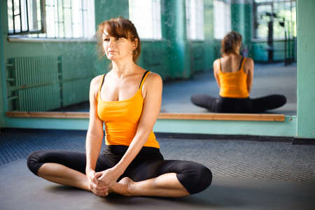 Mature woman exercising yoga in a gym Stock Photo